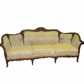Antique Carved Wooden Sofa: An antique carved wood sofa. The sofa has a wooden frame with decorative carvings. It is covered in a cream colored fabric. The sofa is unmarked. It matches chair item 121 and is similar to chair item 123 in this sale.