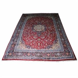 Vintage Handknotted Persian Mashad Wool Rug: A vintage handknotted Persian Mashad wool rug. The rug is handmade in red, blue, cream and navy. It has cream colored fringe at two ends.