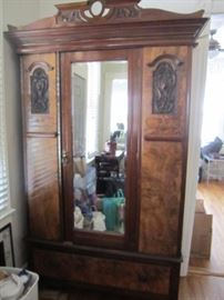 Antique armoire with walnut veneer and intricate carving.  Clothing racks inside and storage drawer below.