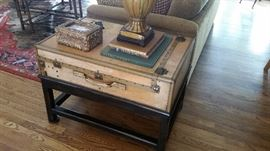 An vintage travel trunk on black custom made stand. Can be used as coffee or end table.