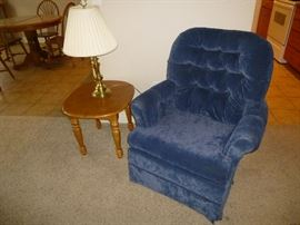 BLUE SWIVEL ROCKER WITH TUFTED BACK. END TABLE AND BRASS TABLE LAMP