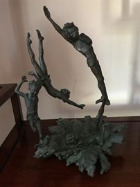 Whimsical bronze statue of three boys diving and playing in the water