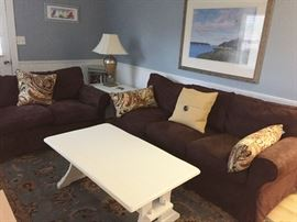Comfy couch, love seat, coffee & occasional tables, book shelf, rug, & home decor!