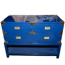 Blue Chest of Drawers with Gold Tone Accents: A blue chest of drawers with gold tone accents. This chest is composed of a wooden frame with a blue veneer exterior. It is complete with two small drawers, and one large drawer with a shelf space below. It has gold tone accents and handles.