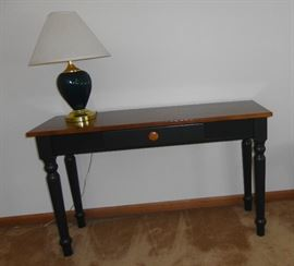 Small sofa table painted dark green, plain dark wood top and middle drawer