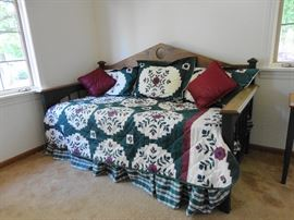 Large trundle bed with dark wood headboard and side rails painted dark green