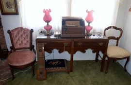 antique cherry side board with a pair of fancy cranberry lamps by fenton
