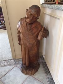 Wood carving of Monk with bottle of wine