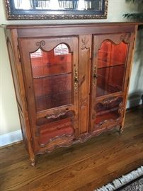 "Lighted display cabinet. Measures 16"" deep by 48"" wide by 50 1/2"" tall. No visible manufacturer's marks."