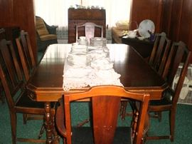 Another view of the beautiful table with 3 leaves, table pads, six chairs and matching buffet and china cabinet.