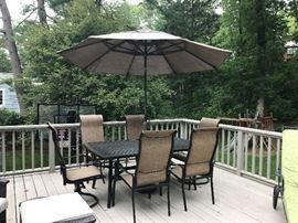 Like new Patio set with six armchairs and matching umbrella in neutral weather resistant fabric with ergonomic curves.  Two on swivel pedestals.