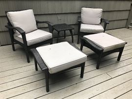 Pair cushioned patio basketweave armchairs with matching ottomans and side table.