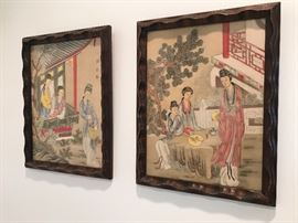 Three Coordinating Pieces of Asian Artwork depicting groups of people in traditional scenes.  Professionally Mounted in Carved Dark Stained Frames.