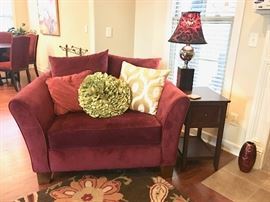 Double-love couple-sized arm chair with a few of the numerous attractive throw pillows and one of numerous decorative lamps