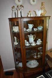 American Oak Curved Glass China Cabinet filled with Collectible items including Chocolate Set, Footed Case Glass Bowl with Fluted Edge, Willow Tree Figurines and more!