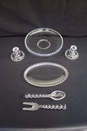 "Clear Hostess Set: including 12"" float bowl & 10"" salad servers by Imperial of OHIO, Candlewick pattern, and pair of 4-1/2"" candlesticks and oval 12"" dish by Anchor Hocking. This lot is in very good condition and shows little wear, if any."