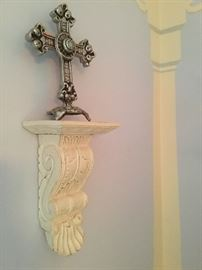 One of many wall shelves with a good looking silver plate cross