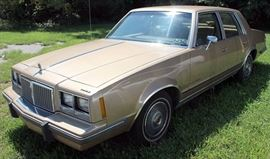 At 8PM: 1986 Pontiac Bonneville Estate Auto with 84,590 Odometer Reading; Gold Metallic Exterior, Tan Cloth Interior; AM/FM Stereo; Air Conditioning; Clean & Well Maintained. VIN: 2G2GN69A0G2288422