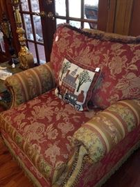 One of two over-stuffed red/gold chairs
