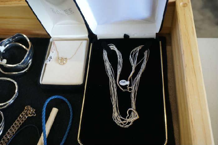 Sterling necklace                                                                    10KT gold & diamond horseshoe necklace on left