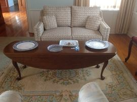 Love Seat converts to a twin hide a bed, coffee table and a handmade, handwoven, Chinese rug.