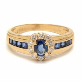 18K Yellow Gold Natural Blue Sapphire Diamond Ring: An 18K yellow gold ring featuring a natural blue sapphire surrounded by a wreath of diamonds with additional natural blue sapphires to the shoulders.
