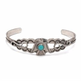 """Sterling Silver and Turquoise Thunderbird Cuff Bracelet: A stirling silver and turquoise thunderbird cuff bracelet. This southwestern style cuff bracelet displays a thunderbird with a round turquoise stone cabochon to the center. The scalloped two layered sides are decorated with decorative stampings of arrows, sun rays, with other patterned markings featuring an applied curled rope to each side. Marked to the inside is """"Sterling"""". The total approximate item weight is 0.355 ozt, inclusive of all materials."""