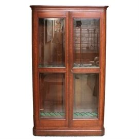 Solid Cherry Gun Cabinet: A solid cherry wood gun cabinet. This piece features cherry construction with beveled glass double doors and sides. It has an overhead light and keyed lock. Cabinet features a felt lined gun rack to the interior with molding to the exterior crown.