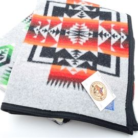 "Vintage Pendleton Wool Blanket: A vintage Pendleton wool blanket. This piece is from the ""Pendleton Indian Friendship"" collection. It features a red, orange, black, and green geometric pattern on a grey ground and is bordered in black. Paper hang tag is still attached. It also has a sewn on maker's tag present."