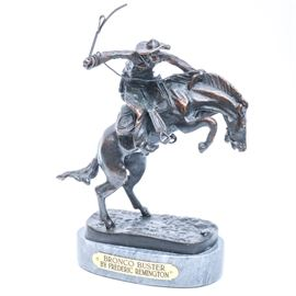 "Reproduction of Frederic Remington's ""Bronco Buster"": A reproduction of Frederic Remington's Bronco Buster bronze statue. This bronze depicts a cowboy on a bucking bronco. Piece is signed in the mold and rests on a marble base with brass plaque. Frederic Sackrider Remington (1861 – 1909) was an American painter, illustrator, sculptor, and writer who specialized in depictions of the old American west."