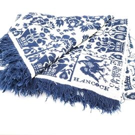 "Signed Antique Hand Woven Blanket: An antique, hand woven blanket in indigo and white. This wool blanket has a repeating floral motif throughout and bares a majestic Federal eagle in deep indigo above a signature which reads, ""Hancock Co + Ohio, J. Fleck, 1851."" This signature and eagle is repeated to the opposite edge of the same side of this charming example of the ethnographic textile arts."