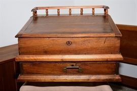 This vintage piece has a slanted top which lifts up and there is a wooden cash box in the bottom drawer.