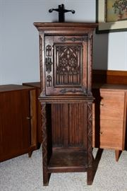 We have not identified this very interesting cabinet yet.  But, it is 49/50in high.  The church window carvings on the front of door appear to be hand chiseled.  The piece was sold by Meubles D'Art in Brussels.  Sticker is on back giving old address of store.