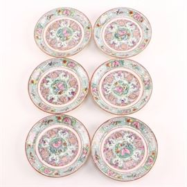 "Circa 1970s Hong Kong Exportware Porcelain Plates: A set of six circa 1970 hand painted porcelain plates. These feature shou medallions surrounded by intertwining pink blossoms and green foliates in the center, and alternating floral and leiwin decoration on the flaring rims. Each piece is marked underneath in red ""Japanese Porcelain Ware"", ""Decorated in Hong Kong"", and ""A.C.F""."