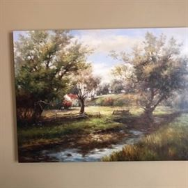 """Embellished Giclee on Canvas of a Wooded Clearing: An embellished giclee on canvas of a wooded clearing. This print with a lacquered finish depicts a small river running through a clearing in the woods and a wooden fence. A decal reading """"Assembled in Mexico"""" are present to the verso of the frame."""