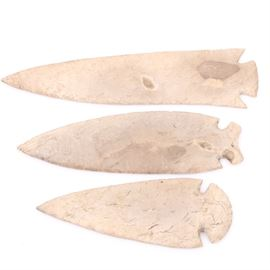 """Double Notched Bifacial Stone Knife Blades: A grouping of three stone double notched bifacial knife blades. The provenance of these blades is unknown. Also included is an artist signed poster titled, """"East Wenatchee Clovis Site, WA""""."""