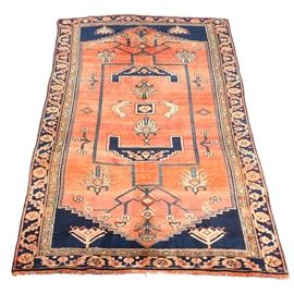 Vintage Hand Knotted Persian Karajeh Heriz Area Rug: A vintage hand knotted Persian Karajeh Heriz area rug. This rug features a peach colored field decorated with geometric shapes and lines surrounded by angular foliate in shades of navy, cream, and cobalt. Navy spandrels sit at each corner and are framed by a compound floral border. The rug finishes with natural warp fringe at either end.