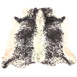 Black and Ivory Cow Hide Rug: A cow hide rug. This hide, with curvilinear edges, features black splotches and patches across the cream and ivory field. The treated underside is off-white.