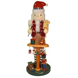 Oversized Nutcracker: An oversized nutcracker . The piece depicts a tall nutcracker figure with a table covered in toys under him. It is in a color palette of red, green, blue, yellow, and brown. It has a smooth finish and is not marked.