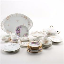 "Selection of German and Limoges Porcelain Tableware Including Jean Pouyat and Theodore Haviland: A selection of tableware from Germany and Limoges, France, including manufacturers such as Jean Pouyat and Theodore Haviland. This thirty piece collection features a pair of plates from Jean Pouyat with an indented edge and light blue and red floral designs painted to their tops; as well as plates, saucers, a teacup, a covered dish, and a covered serving bowl from Theodore Haviland, with a pink floral design, and a subtle textured pattern to the rim of the larger plates. Also included is a teacup and several other pieces from Hutschenreuther Selb, Germany, with purple and white floral designs, and gilt accents; and a pedestal dish marked ""MZ Austria"", among other pieces."