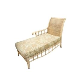 "Braxton Culler Wicker Chaise Lounge: A wicker chaise lounge by Braxton Culler. This piece features a curved rush back and one scrolled arm with criss-crossed supports. It has an openwork apron with vertical supports and rests upon subtle sabre legs. The piece is marked Braxton Culler Furniture"" to the cloth seat."