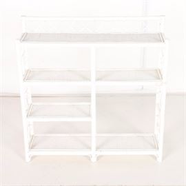 Wicker Shelf: A wicker shelf. This white finished wicker shelf features three rectangular shelves spanning the width of the piece and one rectangular half shelf. The shelves are framed by a wicker floral design.