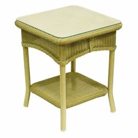 Wicker Side Table: A wicker side table. This wicker table features a square top with a glass cover over a curved apron that rises on four tubular legs terminating in splayed feet. The legs are supported by a shelf stretcher.