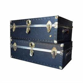 Vintage Steamer Trunks: A set of vintage steamer trunks. This pair of trunks features black exterior lining with brass-tone nail head trim and hardware with a rectangular top lid opening to a paper lined interior. Each trunk includes side handles.