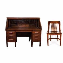 Vintage Roll Top Desk With Matching Chair: An antique roll top desk with matching chair. This pair includes an antique desk and chair made of solid oak. The desk features five drawers with three on one side and two on the other and rows of slots and cubby holes for office accessories. There is a pull-out writing surface on either side above the column of drawers. The front of the desk rolls down. This antique piece is made with intricate dovetail joints and has a varnish finish. There is a single brass accent piece where the roll top latches and locks. There is no key included. This desk is circa 1900. Also included is a matching chair. It has a curved seat back with a slotted design. It too is made of solid oak and has a smooth and polished finish. Both these pieces are unmarked.
