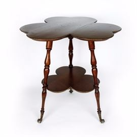 Victorian Parlor Table: A Victorian parlor table. This Victorian parlor table has a clover design. It features a large table surface and smaller matching shelf beneath. The legs have a spindle design with claw and ball feet. There is metal accent trim around both the table surface as well as the lower shelf.