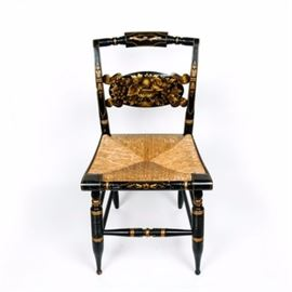 Authentic Vintage Hitchcock Painted Chair: An authentic vintage Hitchcock painted chair. This vintage 1980s chair has a wooden frame and woven, straw seat. The frame is painted black with an ornate gold-toned floral and fruit motif painted across the seat back, legs, and edging. Along the back of the seat, the chair is marked Hitchcock in stenciling.