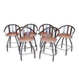 Six Swivel Barrel Back Barstools: A collection of six swivel barrel back barstools. Each stool features an arched and bowed, tubular bar back with a triple slat splat over a tan leatherette seat, resting on a swivel base. The base swivels and includes four curved spider legs in a tube design with a box frame attached to the lower edge for stability and as an integrated foot rest. The metal has an applied bronze finish.