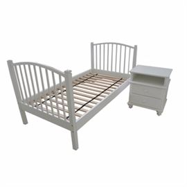 """Contemporary Twin Size Bed Frame and Night Stand by Crate & Barrel: A contemporary twin size bed frame and night stand by Crate & Barrel. This set includes a bed frame with white finish and matching crest rail to the headboard and footboard. The bed incldues side rails and rises on straight legs. The night stand includes a rectangular top over an open front storage compartment above two cabinet doors terminating on tapered feet. A night stand drawer interior is marked """"Crate & Barrel""""."""