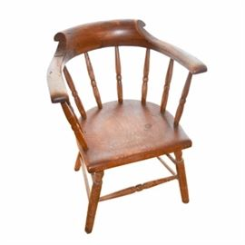 Vintage Windsor Style Armchair: A vintage Windsor style armchair. This armchair features a curved crest rail with an arched backrest to the center supported by turned spindles over a rounded square seat. The seat rises on splayed legs supported by a box stretcher with a turned spindle to the front.